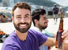Bière potable de type caucasien avec des amis à la plage Photographie stock libre de droits