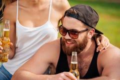 Bière se reposante et potable d'homme de sourire avec son amie dehors Photos stock