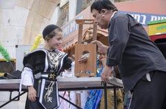 Bière-Sheva, ISRAËL - 5 mars 2015 : Garçon juif dans un costume noir et pile noire sur l'étape avec le magicien - Purim Photos stock
