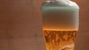 Bière versant dans le verre sur un mouvement lent de fond texturisé banque de vidéos
