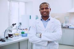 Biólogo de sorriso que está no laboratório fotografia de stock royalty free
