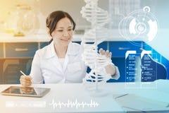 Biólogo feliz que toca no modelo e no sorriso do ADN fotos de stock