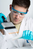 Biólogo joven con la pipeta de varios canales Foto de archivo libre de regalías