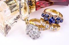 Biżuteria i pachnidło na białej odbijającej powierzchni. Zdjęcie Stock