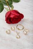 Biżuteria ustawiająca złoty pierścionek, kolczyki, kolia z perłami i czerwieni róża na białym drewnianym tle, Obrazy Stock