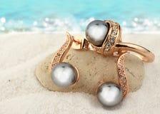 Biżuteria ustawiająca z czarnymi perłami na piasek plaży tle, odbitkowy zdrój Fotografia Stock