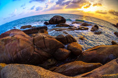 Bi-color sunset on boulder shoreline Royalty Free Stock Images