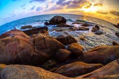 Bi-färg solnedgång på stenblockshoreline royaltyfria bilder