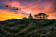 BI-PLANES OVER POINT LOMA, CA SUNSET LIGHTHOUSE royalty free stock image