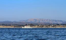 Biała łódź przeglądać od morza przeciw brzeg obraz stock