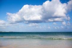 Biała piasek plaża, turkusowy morze na niebieskim niebie z bielem chmurnieje tło obraz stock