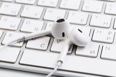Białe słuchawki na białej klawiaturze zdjęcie stock