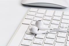 Białe słuchawki na białej klawiaturze fotografia stock
