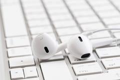 Białe słuchawki na białej klawiaturze fotografia royalty free
