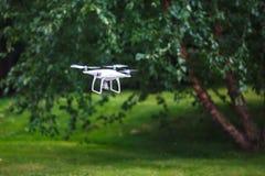 Biały latający quadrocopter z kamerą na zielonym lasowym tle obrazy stock