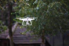 Biały latający quadrocopter z kamerą na zielonym lasowym tle obraz royalty free