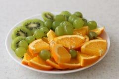 Biały owoc talerz z winogronami, pomarańcze, kiwi fotografia stock