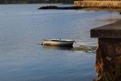 Biała łódź cumował w deptaku Rianxo, Galicia, przy półmrokiem fotografia royalty free