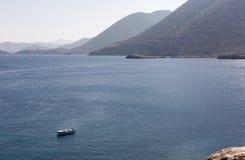 Biała łódź na moorage przy gładką morze powierzchnią przeciw góry tłu Obrazy Royalty Free