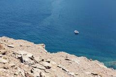 Biała łódź na moorage przy gładką morze powierzchnią przeciw góry tłu Zdjęcie Stock