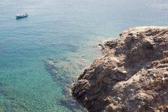 Biała łódź na moorage przy gładką morze powierzchnią przeciw góry tłu Zdjęcie Royalty Free