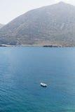 Biała łódź na moorage przy gładką morze powierzchnią przeciw góry tłu Zdjęcia Stock