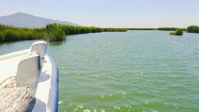 Biała łódź unosi się na rzece z halnym krajobrazem Banki rzeka przerastają z płochami Filmujący dalej zbiory wideo