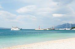 Biała łódź z ludźmi na pokładzie żegluje wybrzeże Obraz Royalty Free