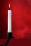 Biała świeczka w starym czarnym candlestick nad czerwienią, obrazy stock
