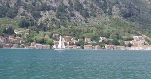 Biała żaglówka żegluje wzdłuż linii brzegowej zdjęcie wideo