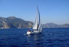 Biała żaglówka unosi się na morzu na tle góry Obrazy Stock