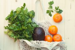 biała życzliwa reusable smyczkowa torba z świeżymi owoc, ziele i warzywami, avocado, pietruszka, pomarańcze na drewnianym tle obraz royalty free