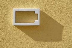 Biała bateryjna ikona na kolor żółty textured ścianie Fotografia Royalty Free