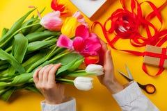Biała caucasian kobieta wręcza trzymać kolorowych tulipany blisko rzeczy Fotografia Royalty Free