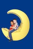 Biała chłopiec i czarny dziewczyny obsiadanie na księżyc Zdjęcie Royalty Free