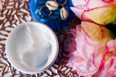 Biała ciało śmietanka w otwartym plastikowym słoju z menchia kwiatami i złotymi kolczykami w składzie fotografia royalty free
