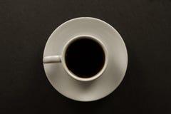 Biała czarna filiżanka kawy na czarnym tle Obraz Stock