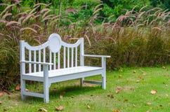 Biała drewniana ławka w ogródzie obraz stock