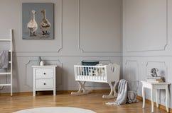 Biała drewniana kołyska z szmaragdową poduszką i zabawkami w kącie elegancki scandinavian dziecko sypialni wnętrze, istna fotogra zdjęcia royalty free