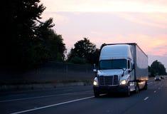 Biała duża takielunku semi ciężarówka z suchym Samochodu dostawczego Przyczepa jeżdżeniem na wieczór zdjęcie stock