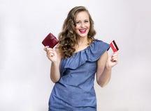 1 biała dziewczyna w błękit sukni z kędzierzawym włosy trzyma czerwonego portfel fotografia royalty free