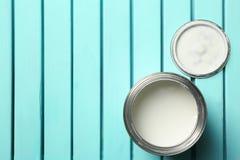 Biała farba może na błękitnym drewnianym tle, odgórny widok zdjęcia stock