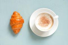 Biała filiżanka cappuccino z świeżym croissant na bławym stole zdjęcie royalty free