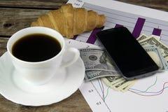 Biała filiżanka czarna kawa, grafika, telefon i dolary, Zdjęcia Stock