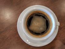 Biała filiżanka czarna kawa z creama stawiającym nad brown drewnianym stołem Fotografia Royalty Free