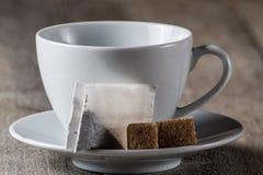 Biała filiżanka dla herbaty, herbacianej torby i kawałków cukier, Fotografia Stock