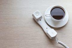 Biała filiżanka i biurowy telefon na drewnianym stole Obrazy Royalty Free