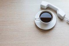 Biała filiżanka i biurowy telefon na drewnianym stole Zdjęcie Royalty Free