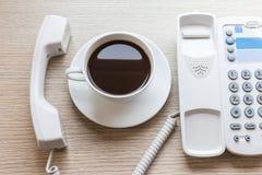 Biała filiżanka i biurowy telefon na drewnianym stole Fotografia Royalty Free