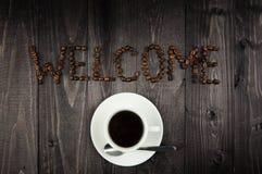 Biała filiżanka kawy i słowo powitanie od kawowych fasoli Zdjęcie Royalty Free